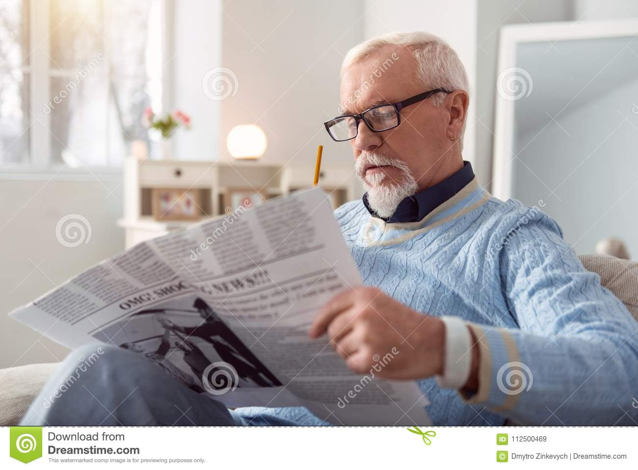 Pleasant Senior Man Reading Article In The Newspaper Stock