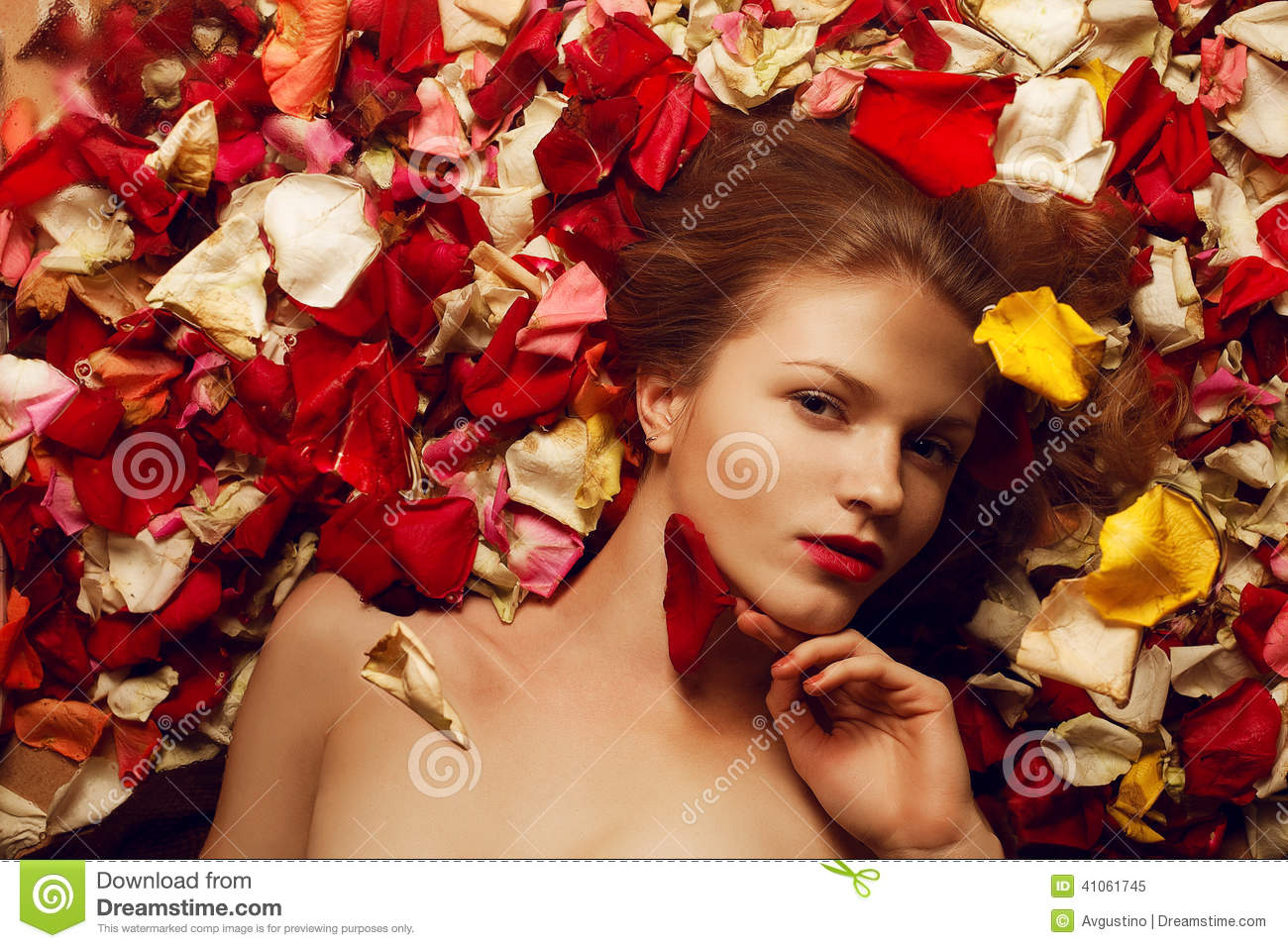 Portrait Of A Fashionable Red Haired Model In Rose Petals