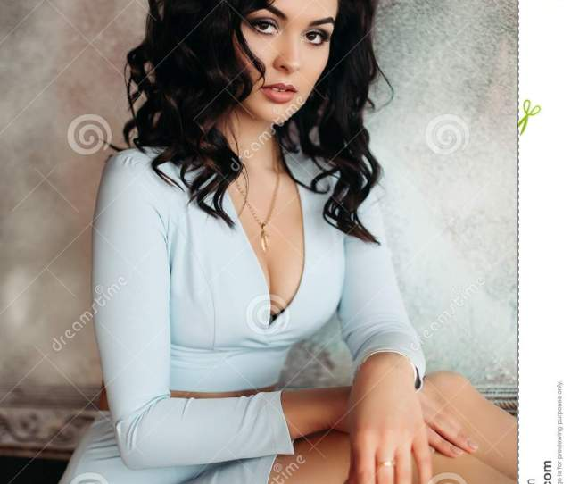 Portrait Of Hot Brunette Woman Wearing In Blue Low Neckline Dress Posing At Camera Gorgeous Girl With Perfect Make Up After Beauty Salon And Volumed