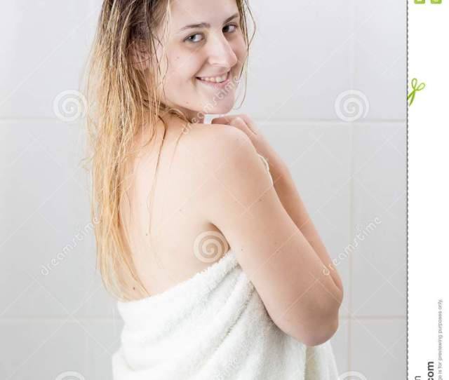 Portrait Of Smiling Blonde Woman In White Towel After Having Shower Looking In Camera