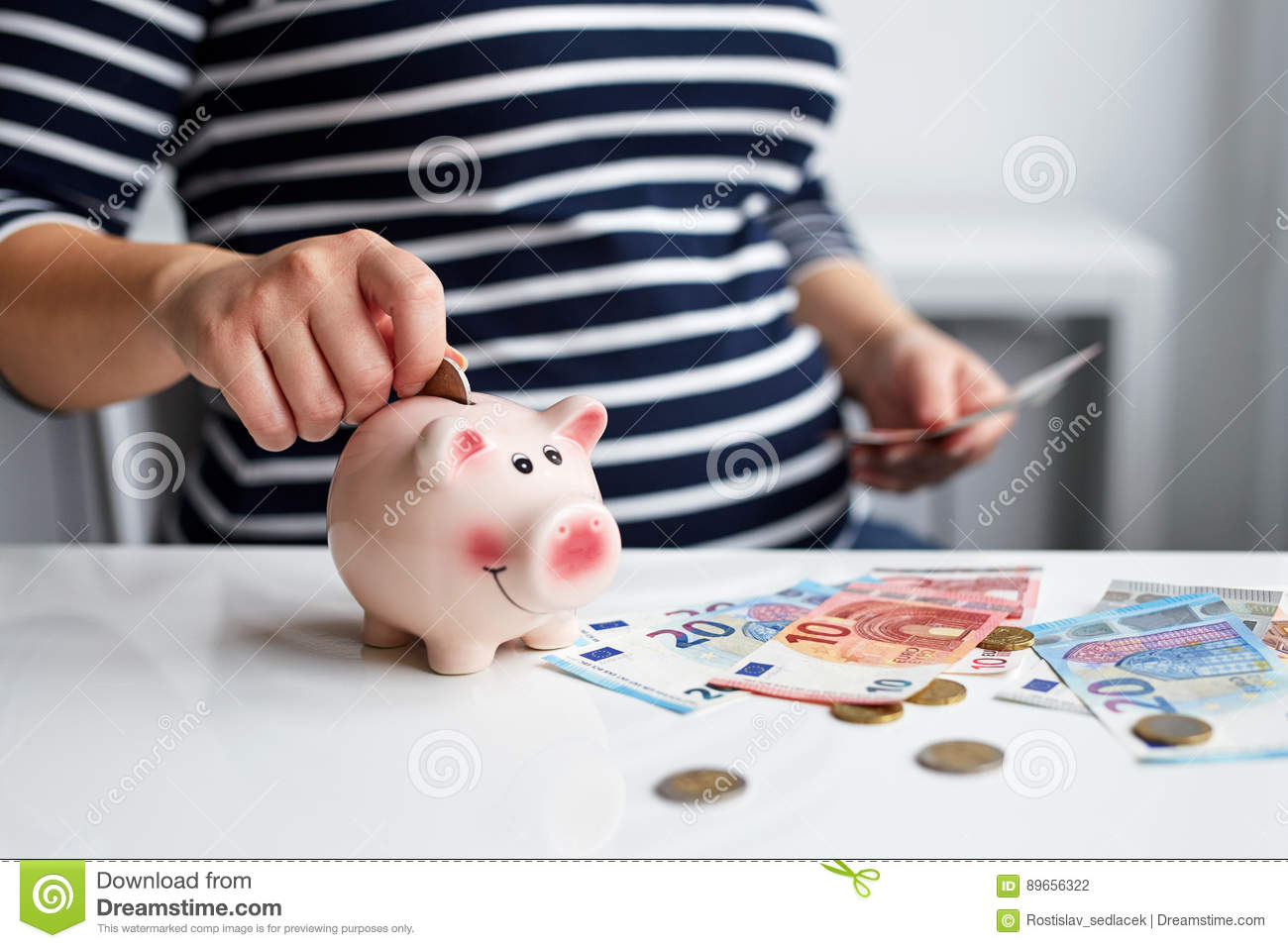 Pregnant Woman Putting Coin Into Piggy Bank Stock Photo