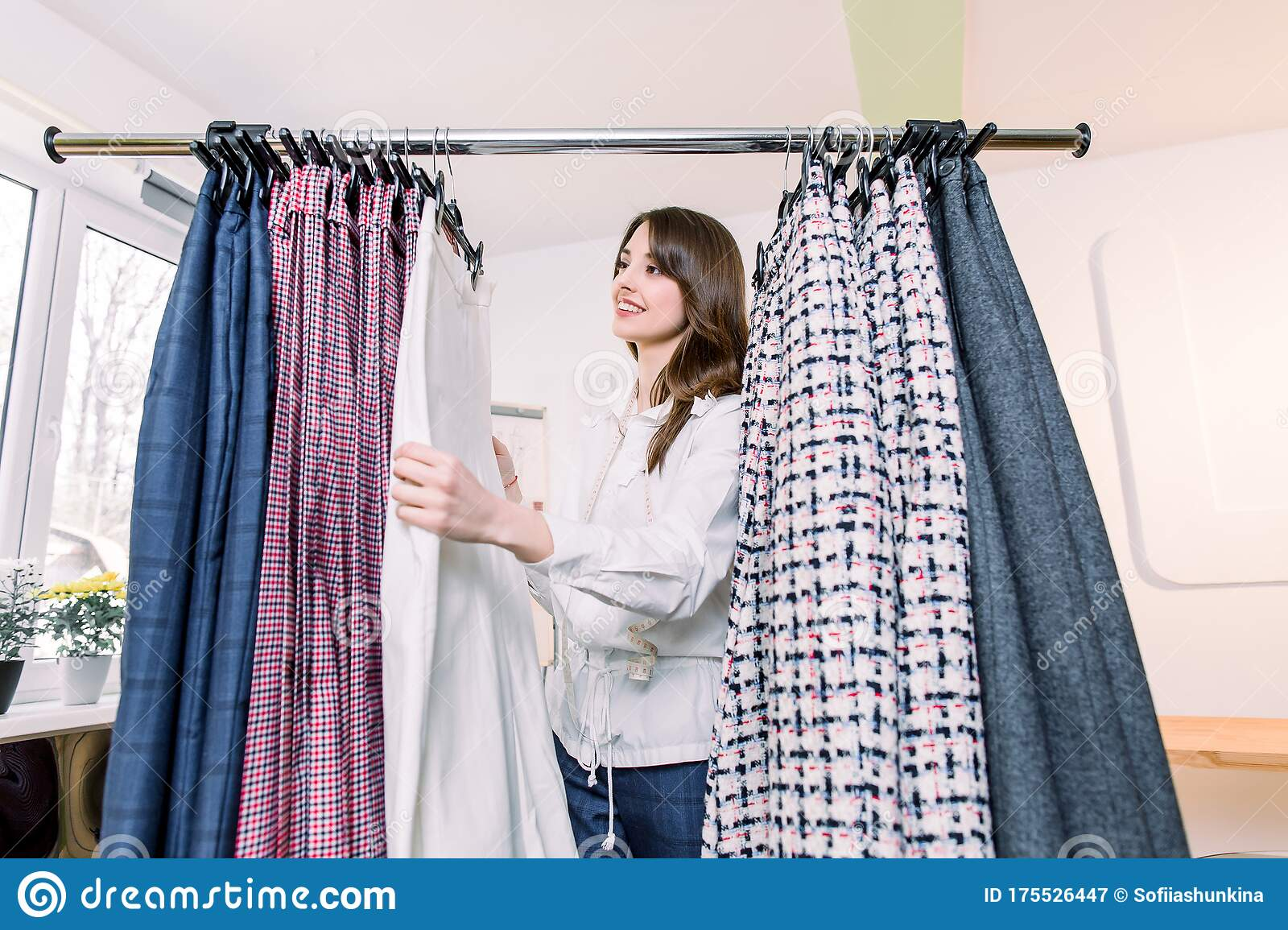 pretty young caucasian female designer or tailor standing near clothes rack with stylish pants working in her atelier stock image image of garment measuring 175526447