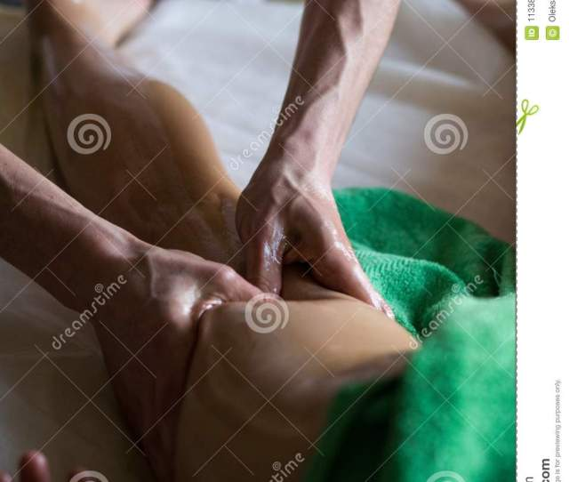 Professional Masseur Doing Deep Tissue Oiled Leg Massage To A Girl At Ayurveda Massage Session