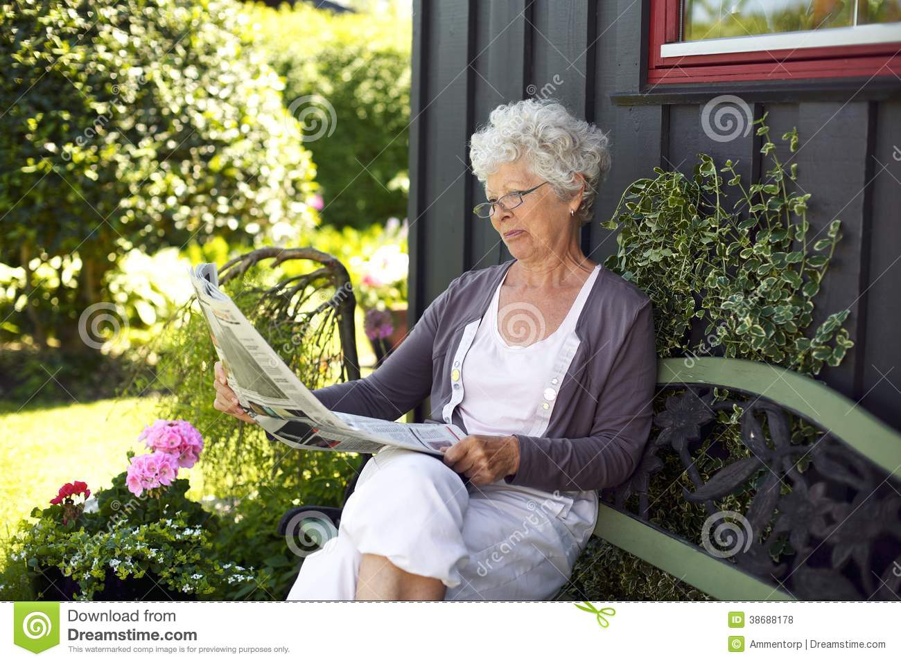 Relaxed Old Woman Reading Newspaper Royalty Free Stock