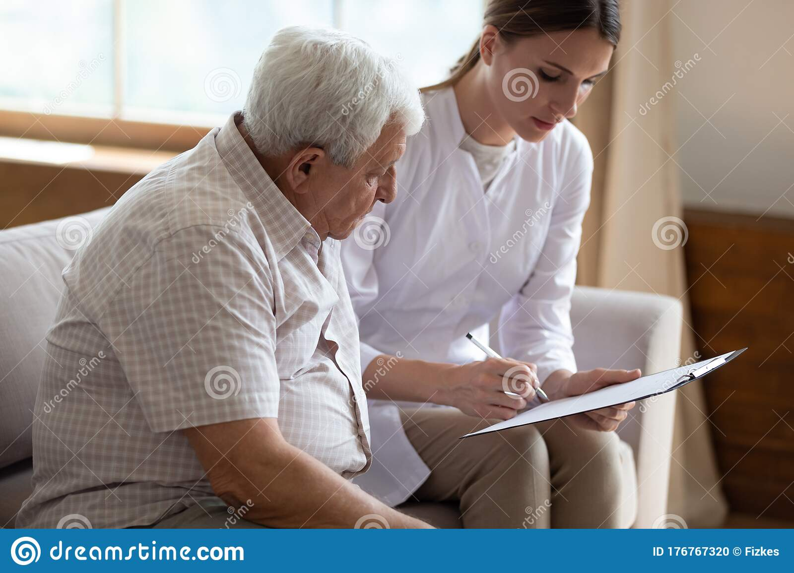 Serious Female Doctor Filling Older Patient Checkup Form