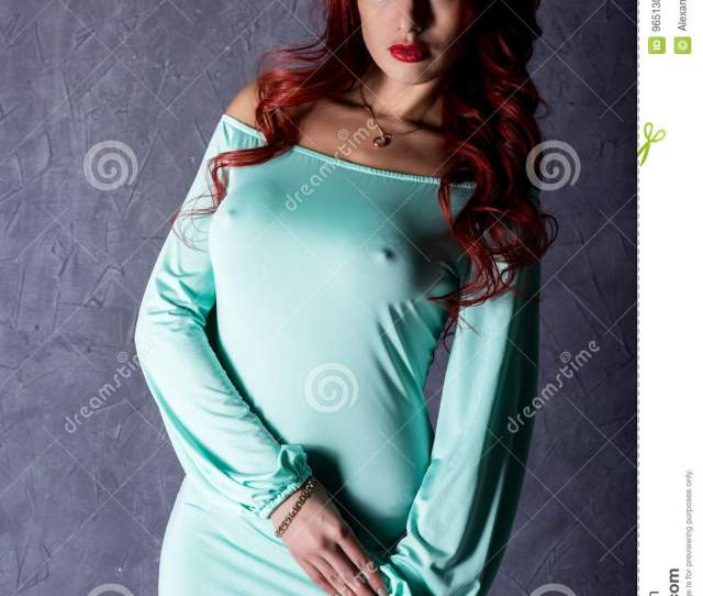Beautiful Redhead Young Woman With Big Boobs In A Turquoise Dress On A Gray Background