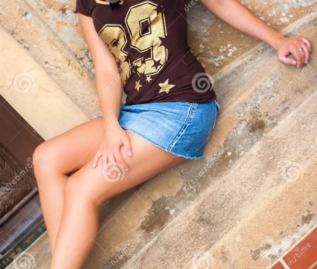 Beautiful And Woman Girl Fashion Model Wearing A Short Denim Mini Skirt Soft Legs And Football Shirt Sitting On Steps
