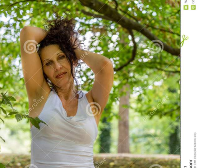 Mature Woman In White Dress Putting Up Her Brown Hair Over A Garden Background