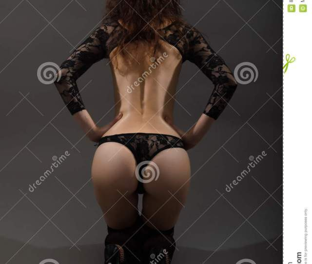 Young Woman With A Big Ass Seen From Behind Woman In Black Bodykit Posing On A Gray Background