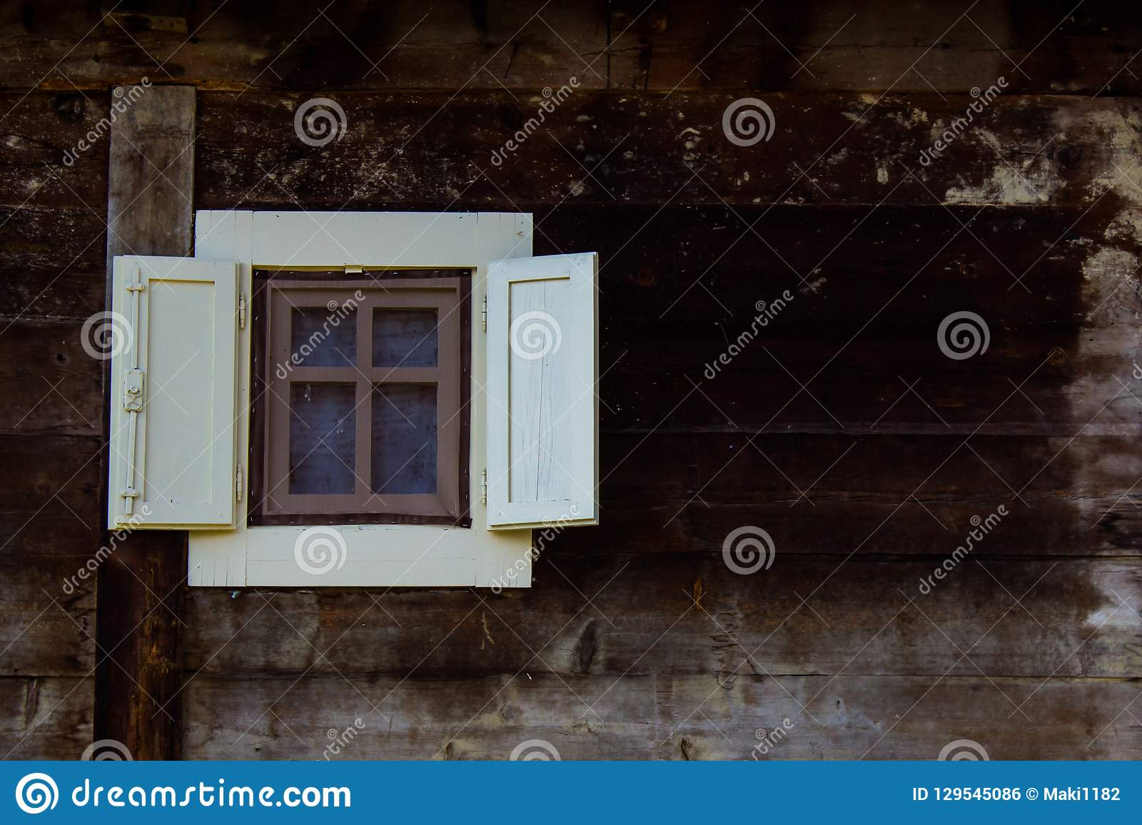 Small Window With Open Shutters On Mountain Wooden House