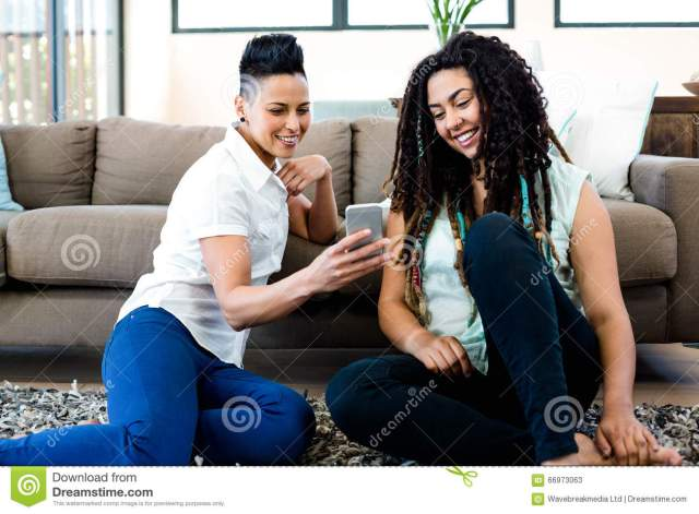 Smiling Lesbian Couple Sitting On Rug And Looking At Their Mobile Phone Download Preview