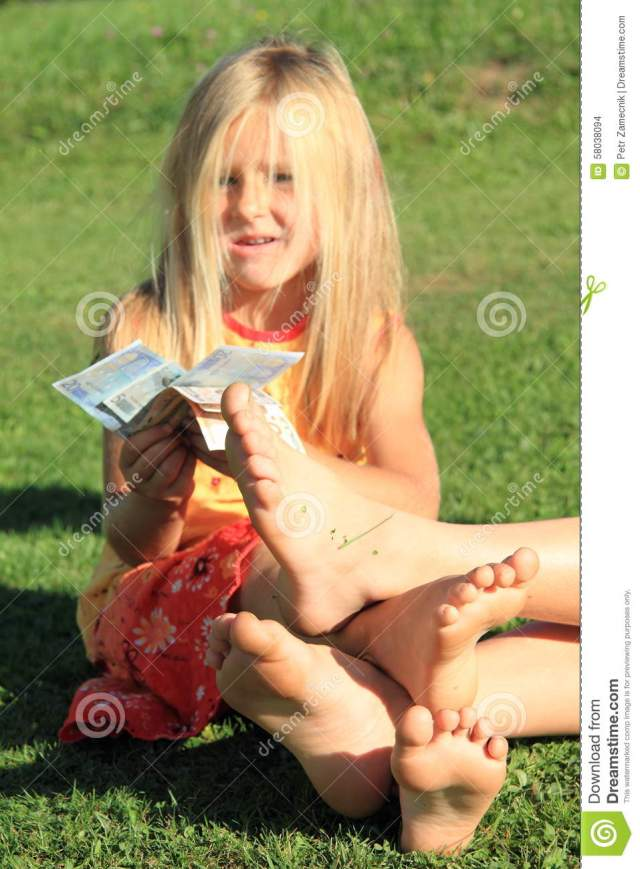 Four Soles Of Bare Feet Of Little Girl And Boy Playing On Grass With Euro Money