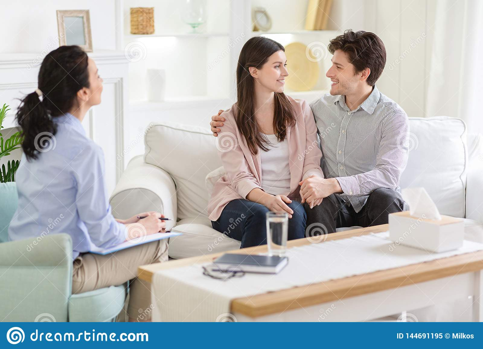 Happy Couple At Successful Therapy Session With Family
