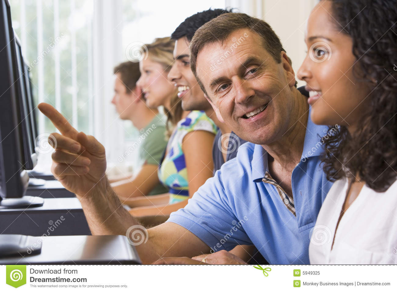 Teacher Assisting College Student On Computers Stock Image