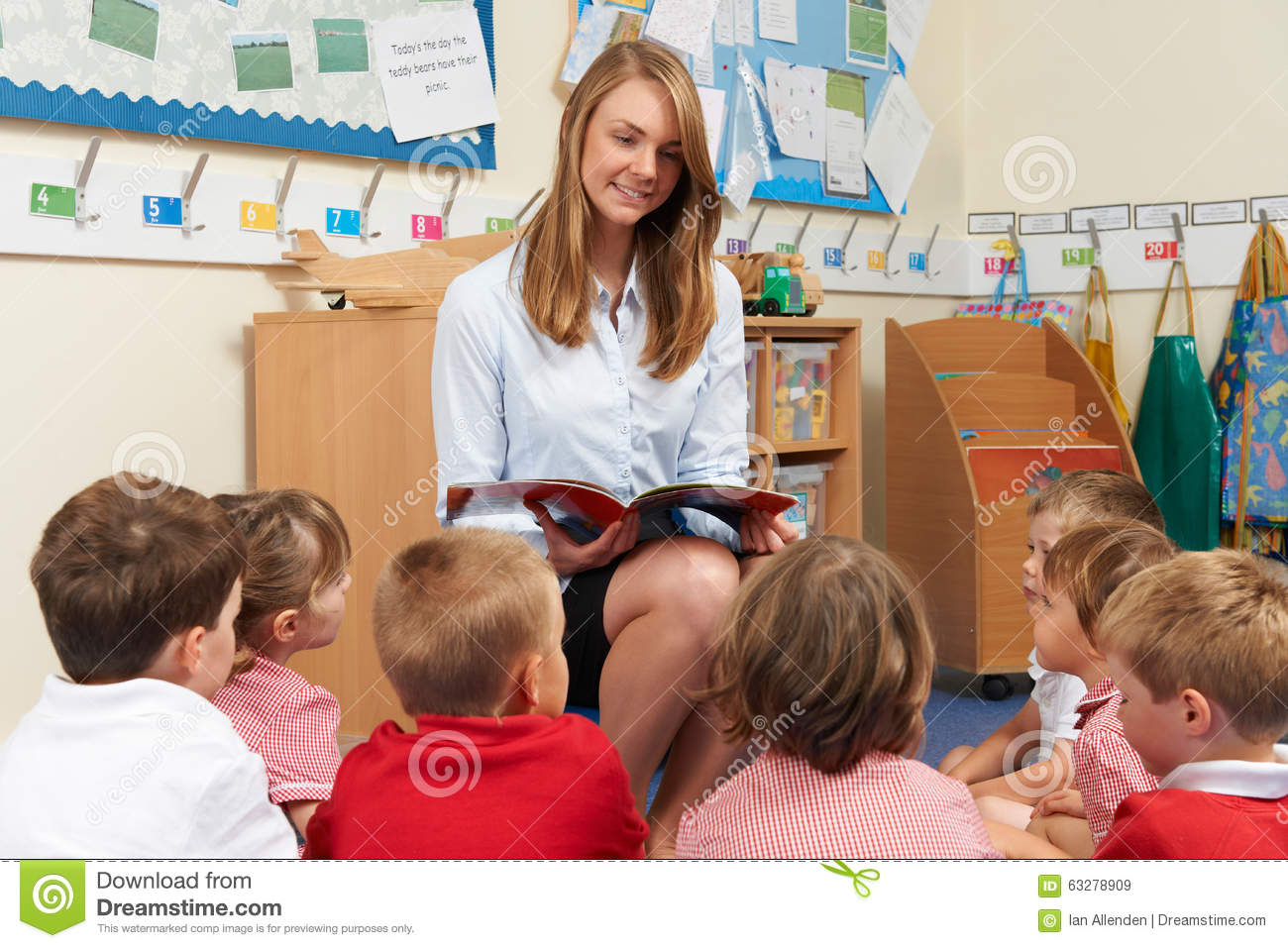 Teacher Reading Book To Elementary School Class Stock