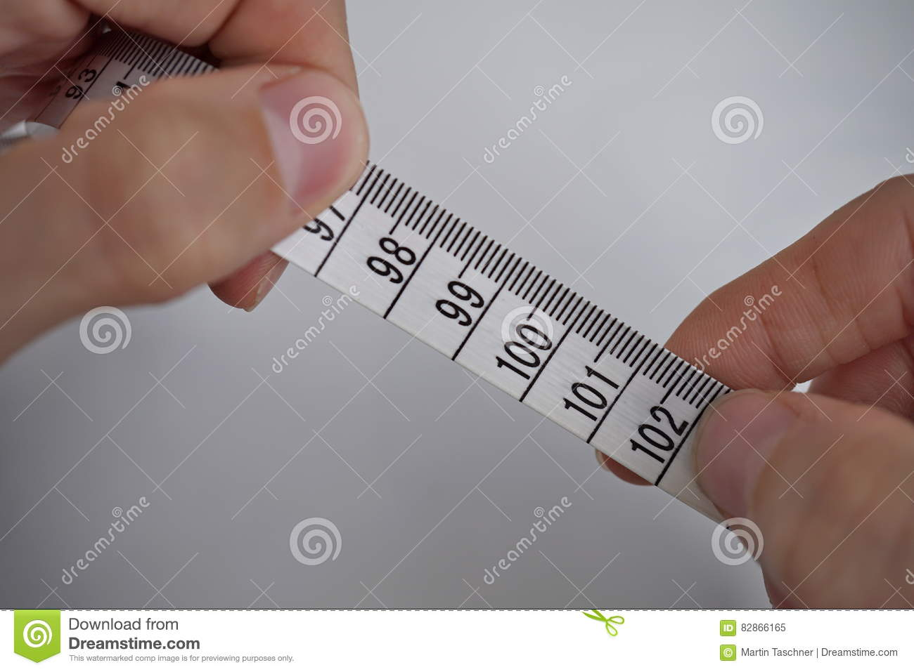 Two Male Hands Holding A Tape Measure Measuring Length In