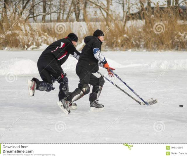 Two Mature Amateur Men Playing Hockey On A Frozen River Dnepr