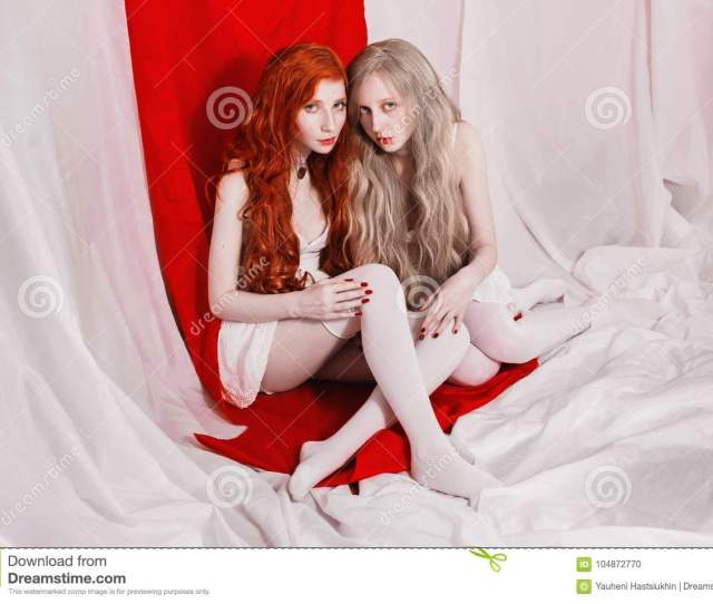 Two Girls With Blue Eyes And Pale Skin On A Red White Background Women Lesbians In White Socks Look At The Camera Blonde And Redhead In White Dresses