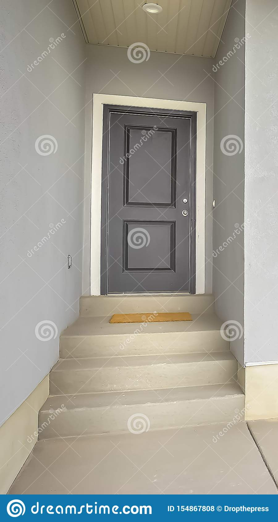 Vertical Front View Of A Home With Gray Front Door And Wood