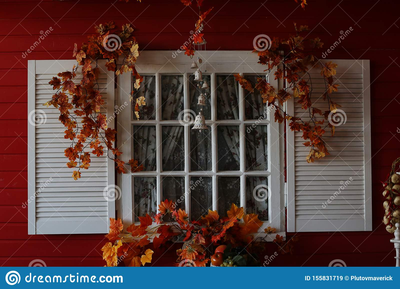 A White Wooden Window With Shutters Decorated In Autumn