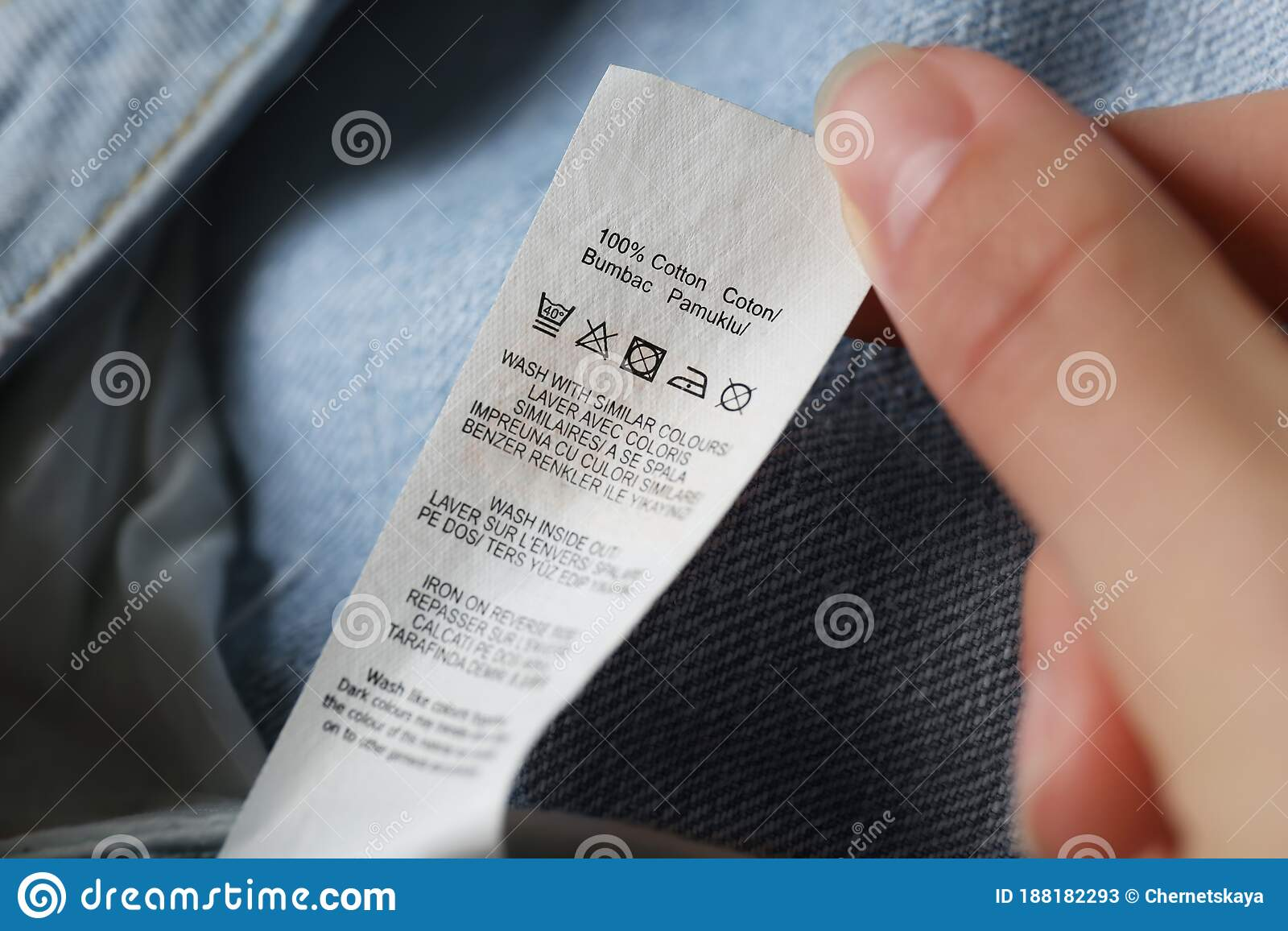 Woman Reading Clothing Label With Care Symbols And