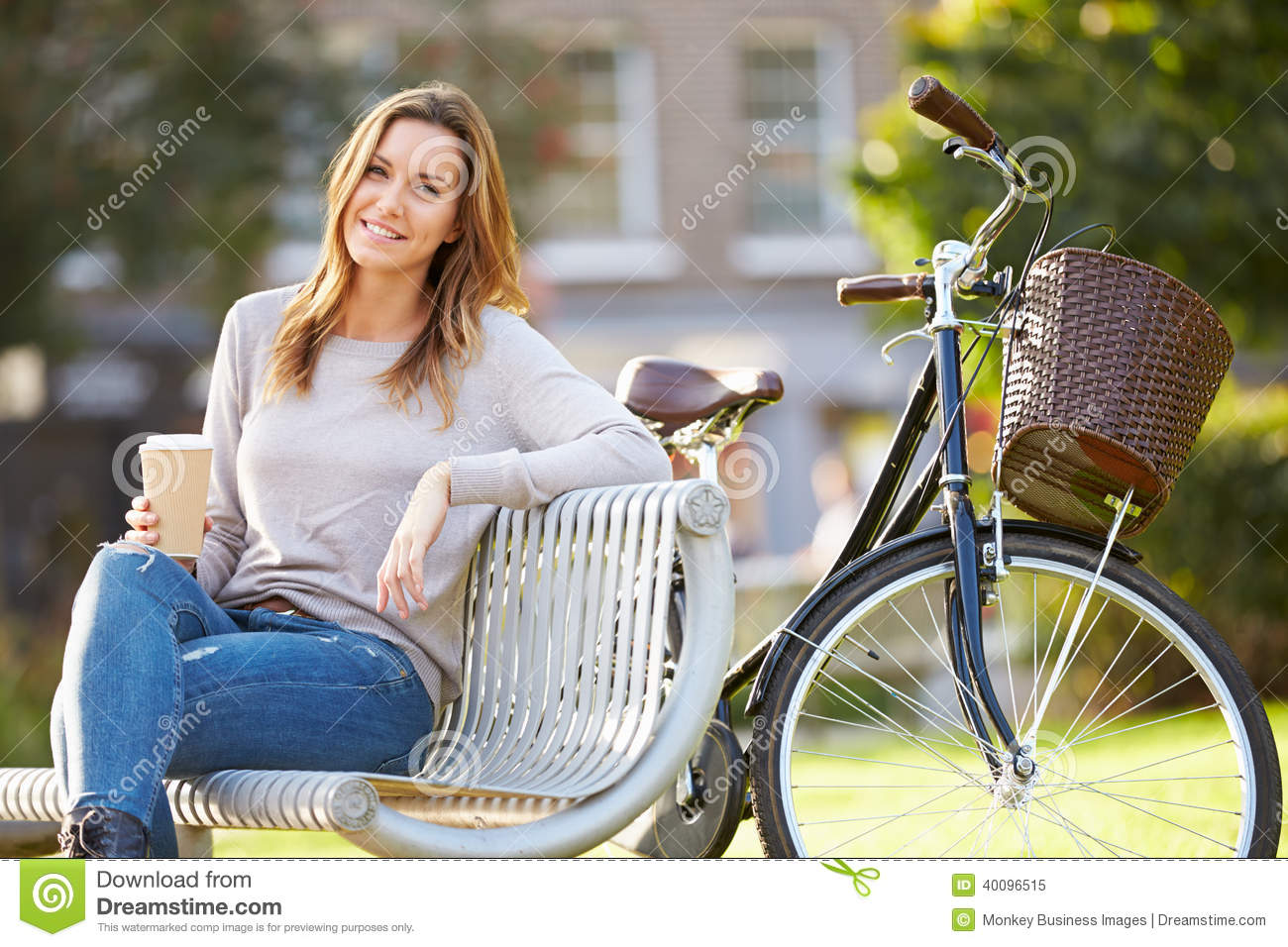 Woman Relaxing On Park Bench With Takeaway Coffee Stock