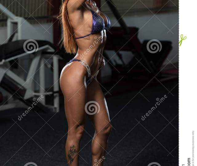 Portrait Of A Young Physically Fit Woman Showing Her Well Trained Body Muscular Athletic Bodybuilder Fitness Model Posing After Exercises