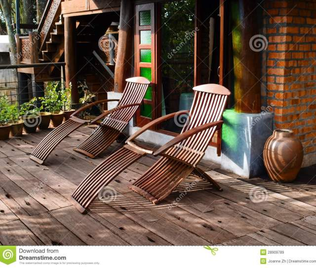 A Photograph Showing Two Curved Wooden Reclining Loungers Seats Placed On The Outdoor Garden Area Of The Patio Or Veranda Of An Old Thai House