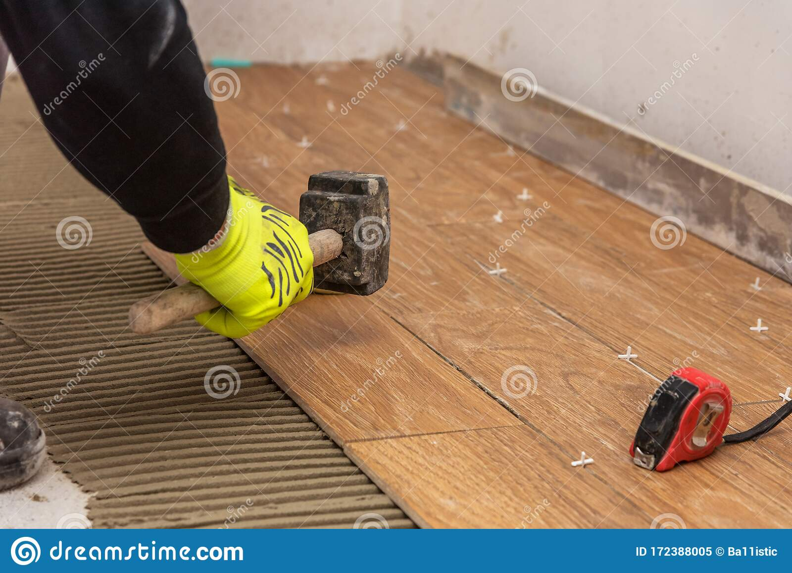 https www dreamstime com worker placing ceramic floor tiles adhesive surface leveling rubber hammer tools tiler installation home image172388005