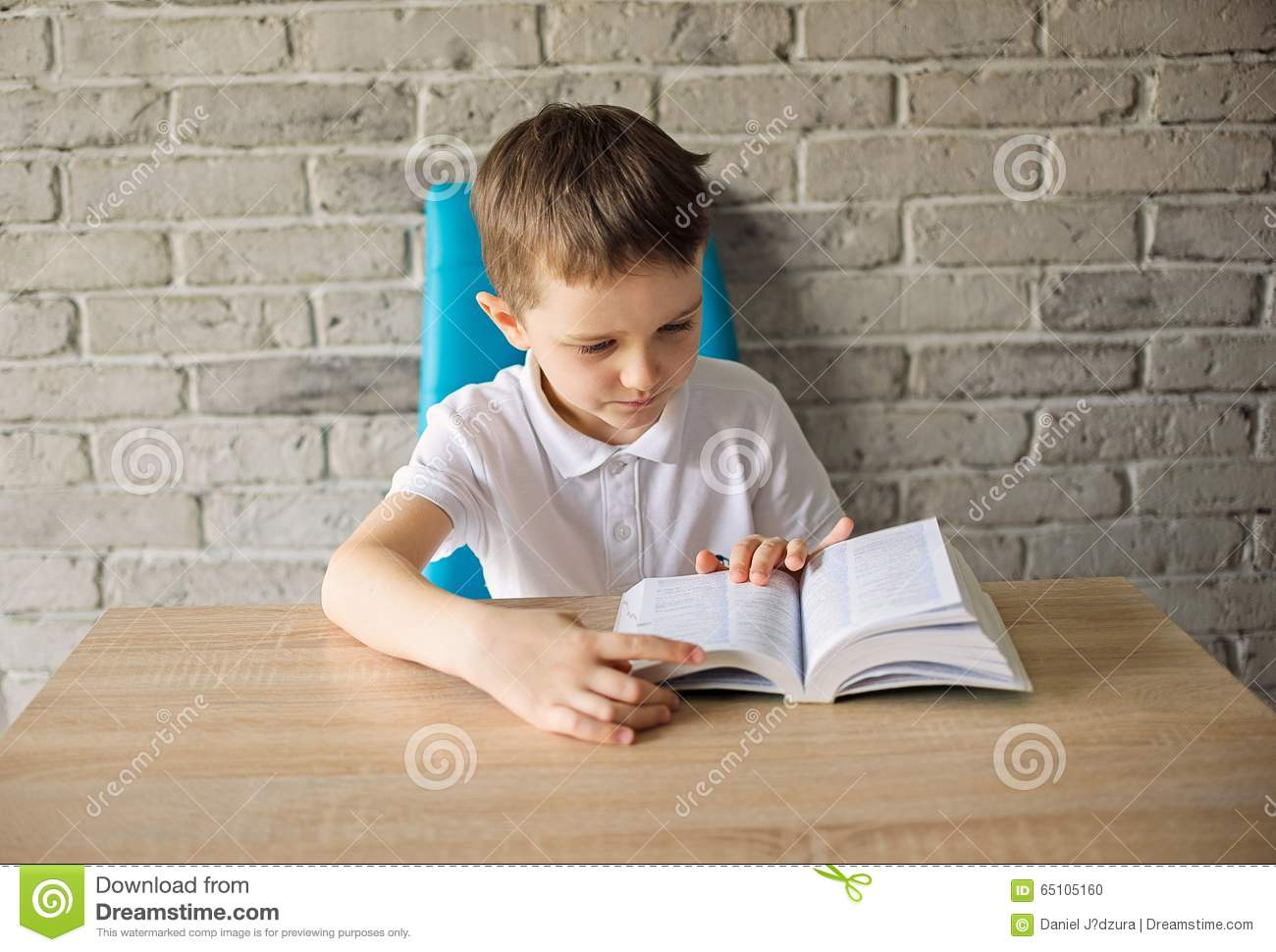 6 Year Old Boy In A White Polo Shirt Reading A Book Stock