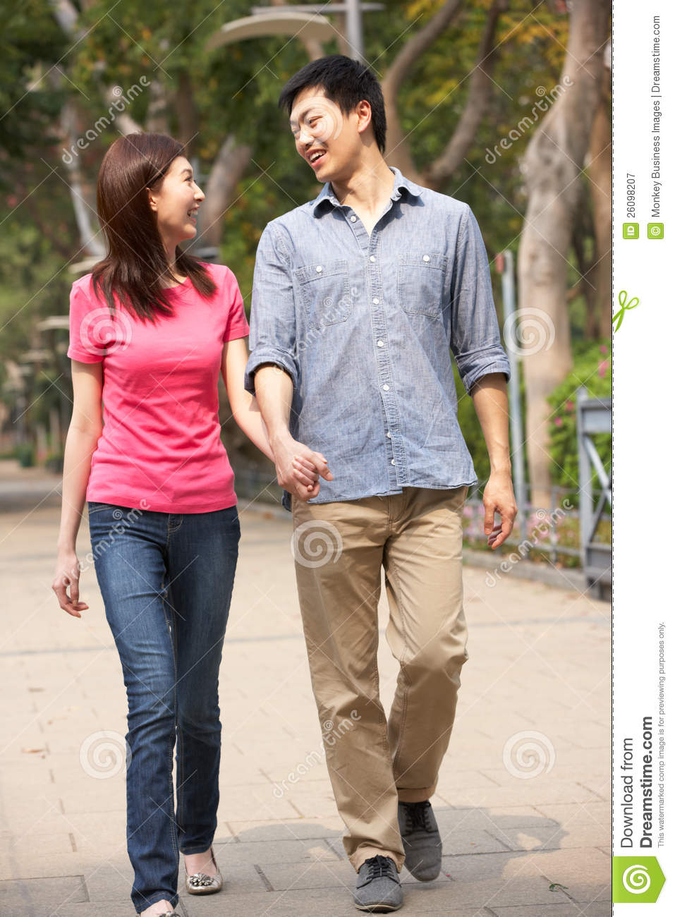 Young Chinese Couple Walking In Park Royalty Free Stock