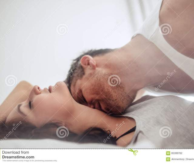 Young Couple On Bed Enjoying Romantic Foreplay