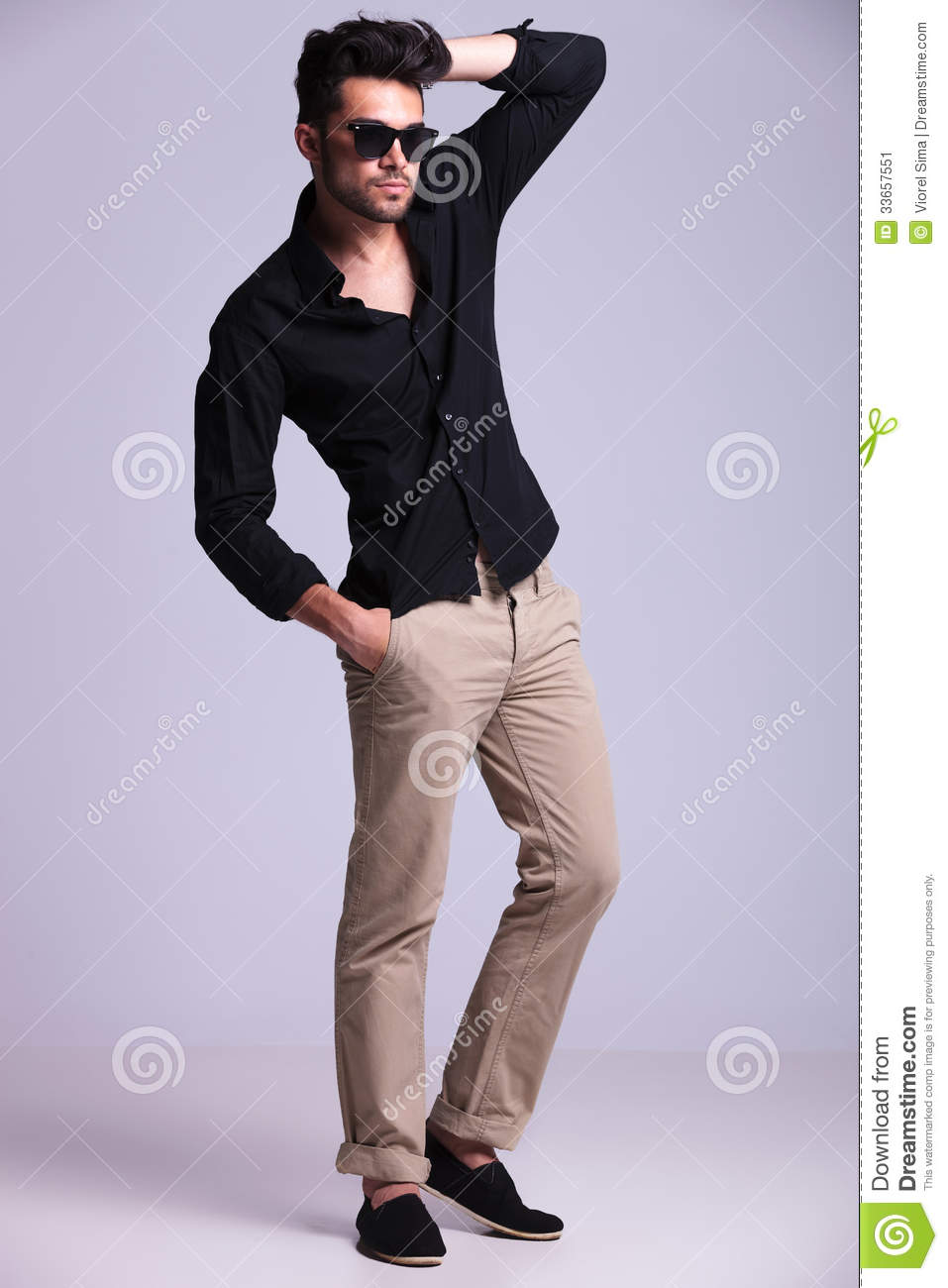 Young Fashion Man Poses With Hand In Hair Stock Image