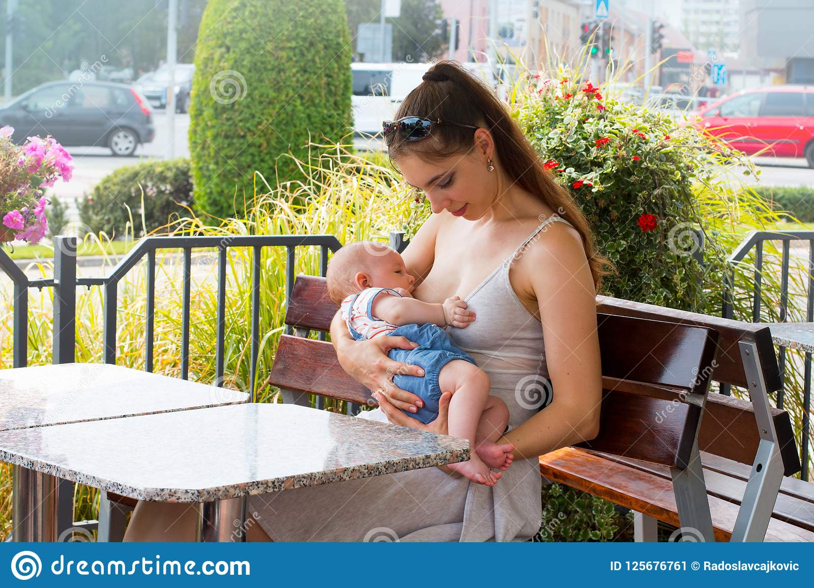 Young Mother Is Breastfeeding Cute Little Baby Outside At