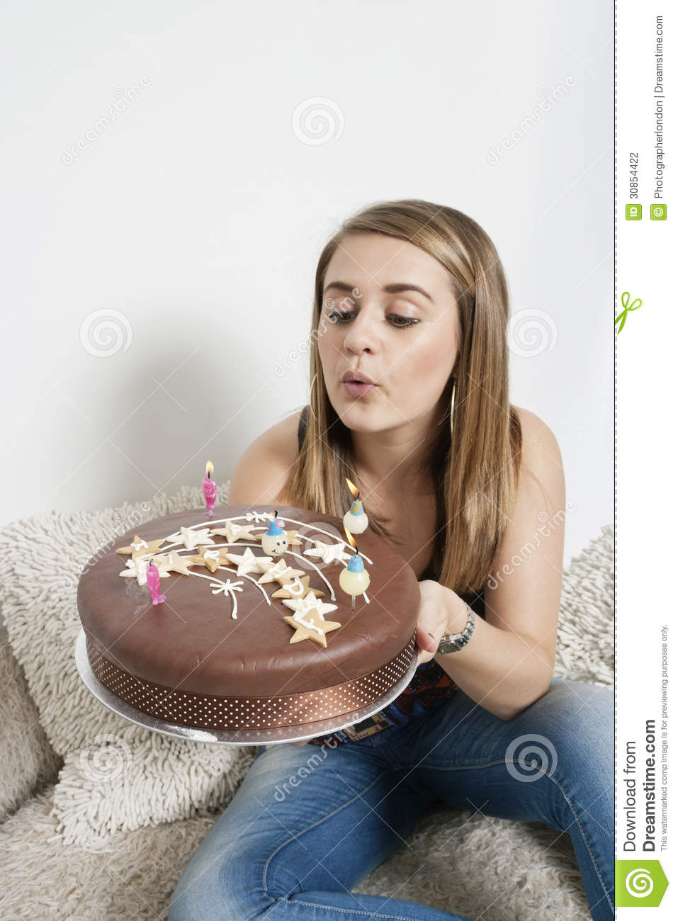 Young Woman Blowing Out Candles On Birthday Cake Stock
