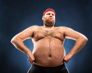 Fat man imitating muscular build. Low angle view
