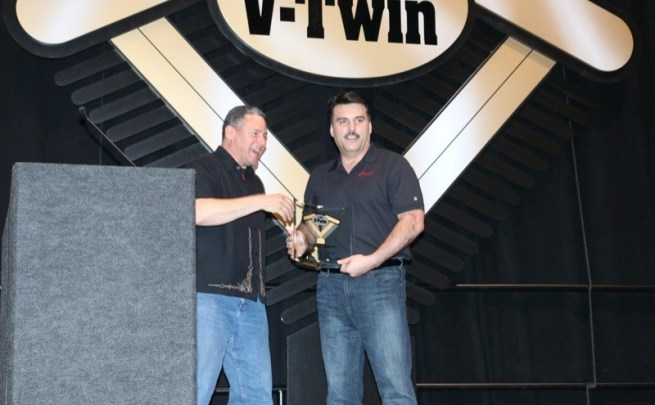 Polaris Industries' Steve Menneto accepts the Industry Leader of the Year award from emcee Griff Allen