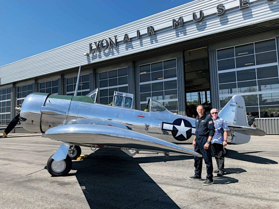 Rich Lewis (right), the winner of the people's choice award with his 1965 Harley-Davidson Electra Glide, prepares to take a flight of a lifetime with Lyon Air Museum President Mark Foster.