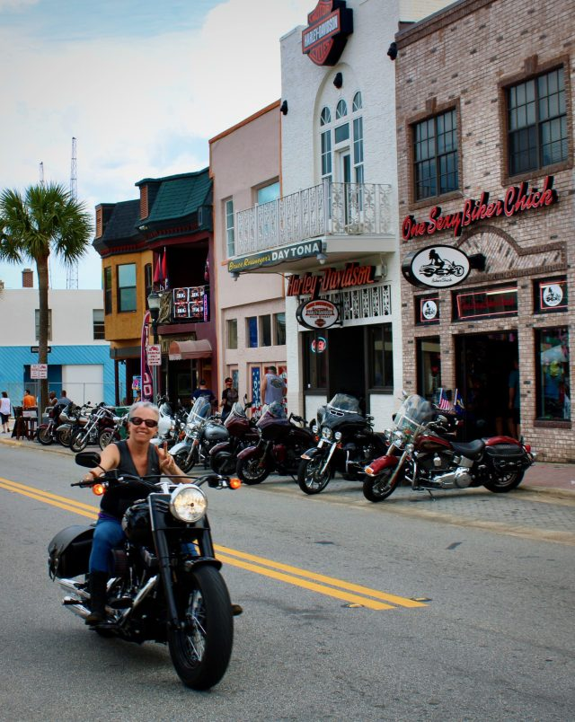 Female biker cruises down Main Street at Daytona Bike Week 2020.