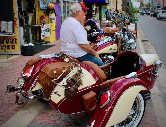 An old biker sits aboard his Indian motorcycle with sidecar along Main Street at Daytona Bike Week 2020.