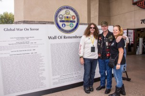 Jay Dabney stands with WCT participants in front of the Wall of Remembrance at Skip Fordyce H-D