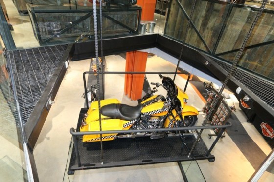 """H-D of NYC's """"taxi bike"""" is showcased on the glass lift between the dealership's two levels"""