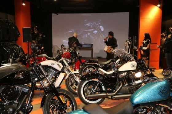 GM/Parts Manager John Maguire and event emcee Felix Rodrigues demonstrate the Power Wall after the dealership's six custom bikes are unveiled