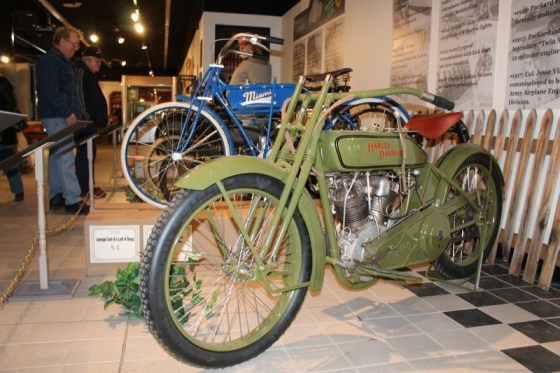 A pristine 1917 Harley-Davidson Model T sits aside a 1916 Miami Power Bicycle