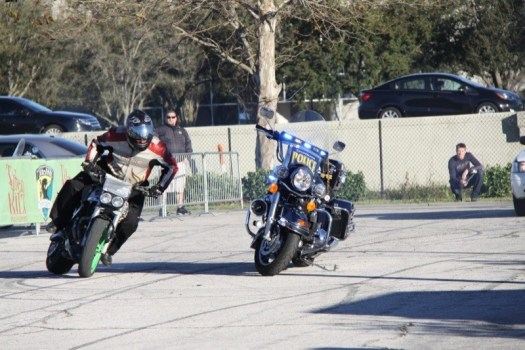 A stunt rider does a high-speed drift around a City of Orlando Police cruiser