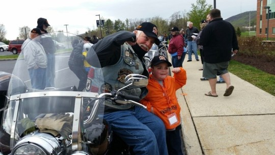 John D'Arcy, owner of Valley Forge H-D, and his sirecar passenger flex some muscle before departing on the Thunder Parade.