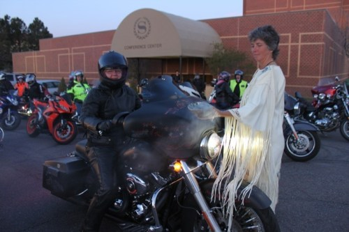 Event organizer Joan Krenning, a.k.a. Lady Road Dog, gets her bike blessed before the ride