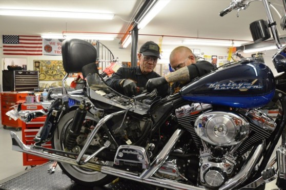 No rest for the wicked, as Kelly works on a customer's scoot during Biker Palooza