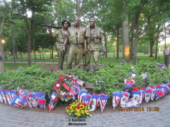 The Three Soldiers statue is littered with bouquets and flags during Rolling Thunder XXVII