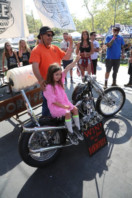 The winner of the Prism built Shovelhead Chopper poses for some pictures with his new best friend, the little girl who was chosen from the crowd to draw the winning ticket
